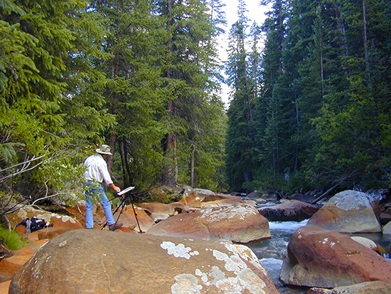 Photograph of John Hulsey painting in a Colorado stream